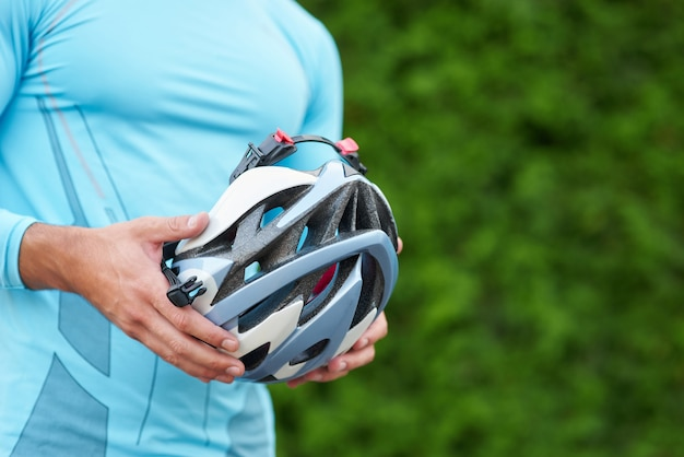 Accessoires de cyclisme gros plan des mains d'un cycliste masculin en tenue de sport tenant un casque de vélo debout