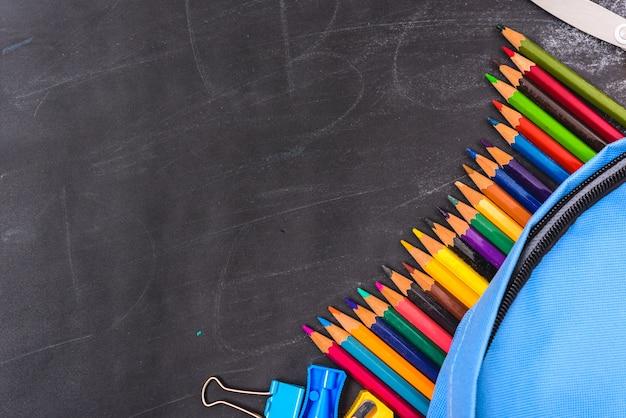 Les accessoires dans le sac bleu étudiant sur tableau noir, concept de sac à dos de retour à l'école