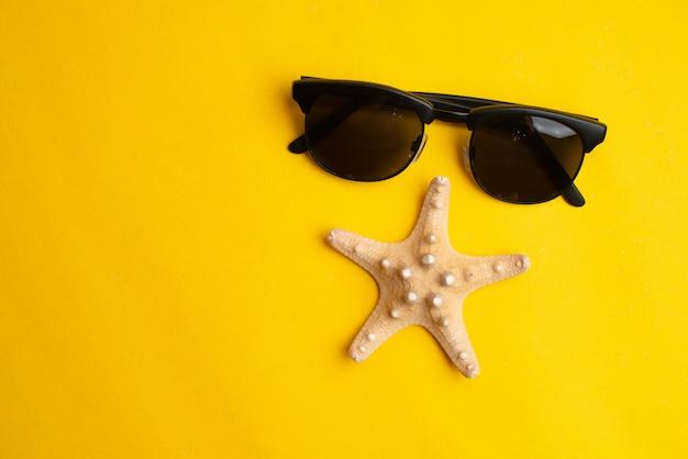 Accessoires d'été, coquillage et lunettes de soleil sur une surface jaune.