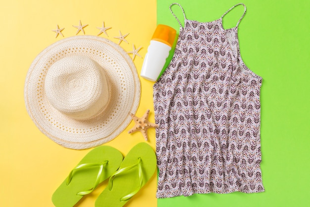 Accessoires d'été avec t-shirt, coquillages, bouteille de crème solaire et chapeau de paille