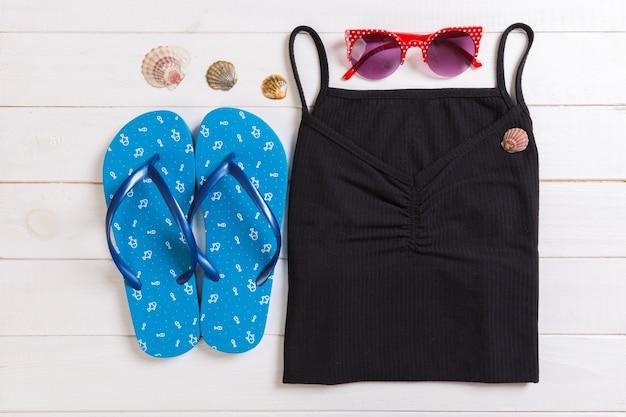 Accessoires d'été avec t-shirt, coquillages et chapeau de paille sur fond de bois blanc vue de dessus à plat.