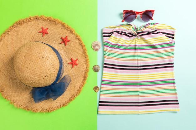 Accessoires d'été avec t-shirt, coquillages, lunettes de soleil et chapeau de paille sur fond bleu et vert vue de dessus à plat.