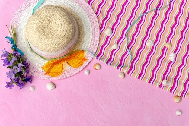 Accessoires d'été sur une table rose.