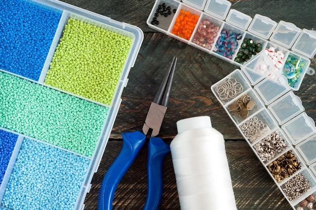 Accessoires faits à la main. boîte avec perles, bobine de fil, pince pour créer des bijoux faits main sur fond de bois ancien. vue de dessus