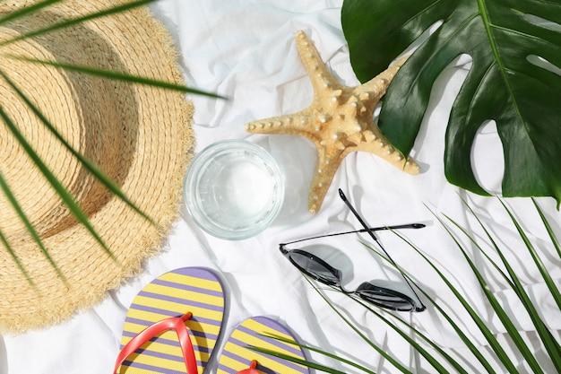 Accessoires féminins sur fond de tissu blanc. concept de blogueur de voyage