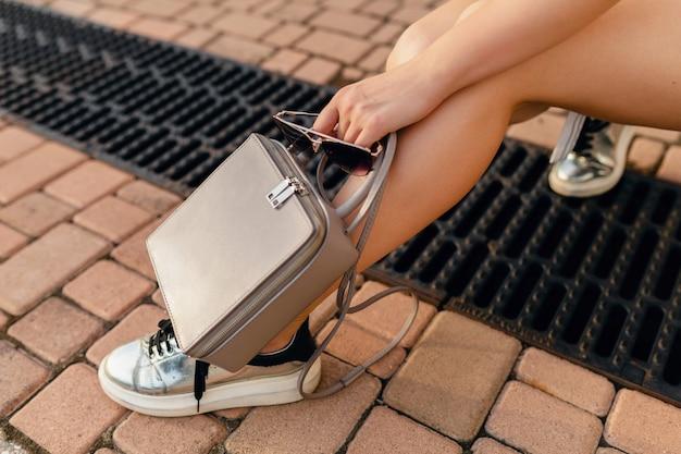 Accessoires de femme élégante marchant dans la rue de la ville en robe de style de mode d'été, baskets, sac à main gris