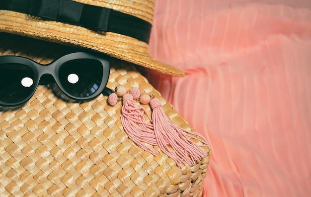 Accessoires femme. fragment d'un sac de paille, boucles d'oreilles, chapeau de paille, lunettes de soleil à la mode noires