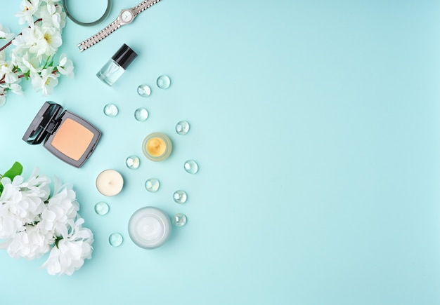 Accessoires femme laïque plate avec crème cosmétique, crème pour le visage, sac, fleurs sur une table bleue pastel