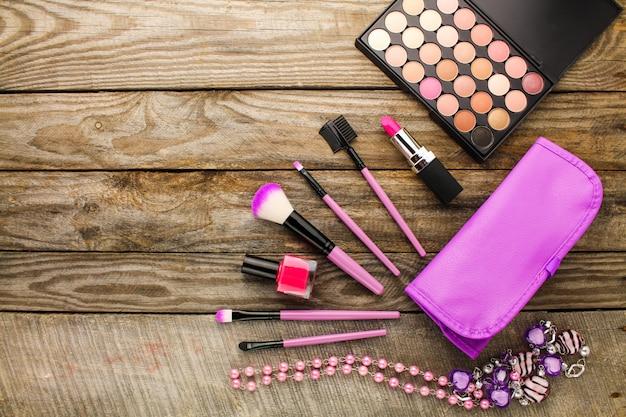 Accessoires femme: trousse de toilette, pinceaux de maquillage, collier, vernis à ongles, rouge à lèvres.