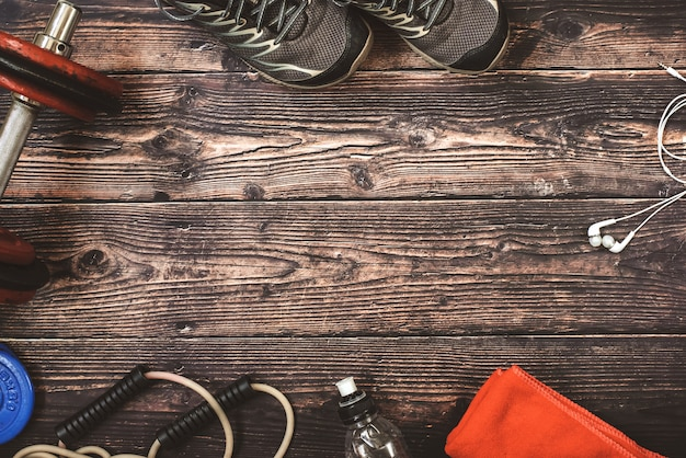 Accessoires de fitness et de sport encadrés à fond, sur du vieux bois.