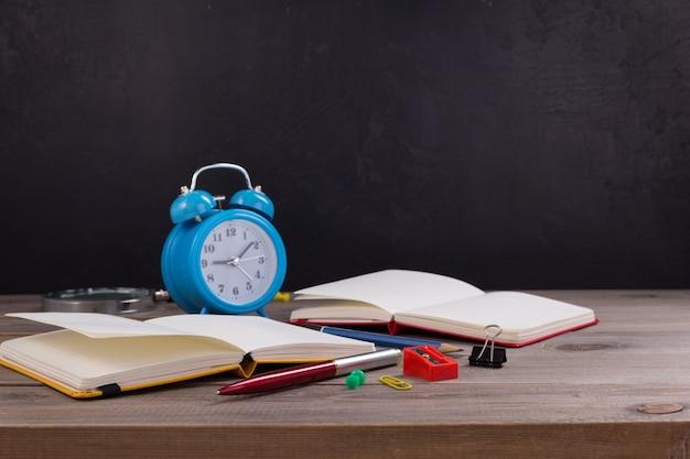 Accessoires et fournitures scolaires avec cahier en papier à la table de surface de fond de table en bois