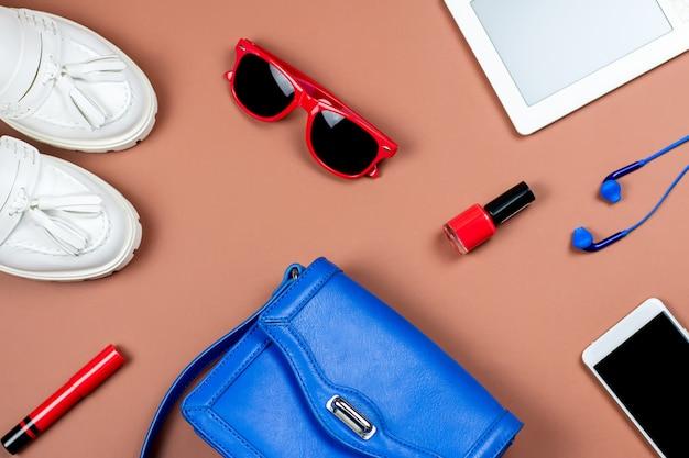Accessoires et gadgets féminins sur fond marron