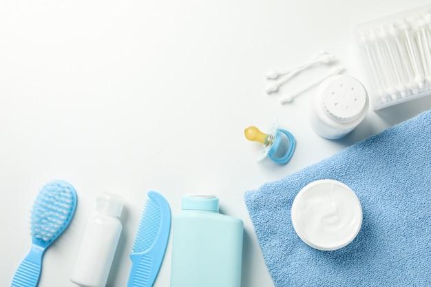 Accessoires d'hygiène pour bébé sur mur blanc, vue de dessus et espace pour le texte