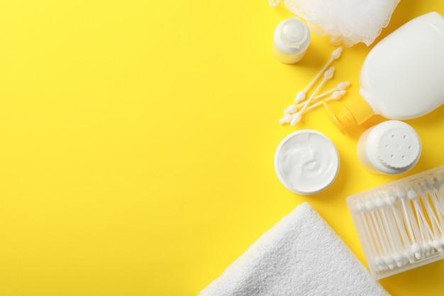 Accessoires d'hygiène pour bébé sur mur jaune, vue de dessus et espace pour le texte