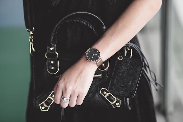 Accessoires de luxe sur la main de la femme avec bague et montre tout en tenant un sac à main noir