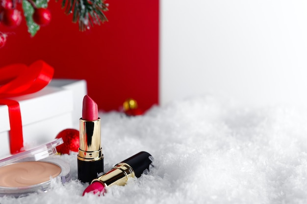 Accessoires de maquillage, produits cosmétiques sur fond de neige. coffret et toile de fond floue de brindille de sapin.