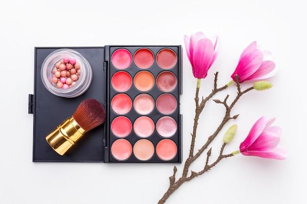 Accessoires de maquillage vue de dessus avec des fleurs