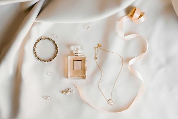 Accessoires de mariée: eau de toilette, boucles d'oreilles, pendentif et bracelet. épouses du matin.
