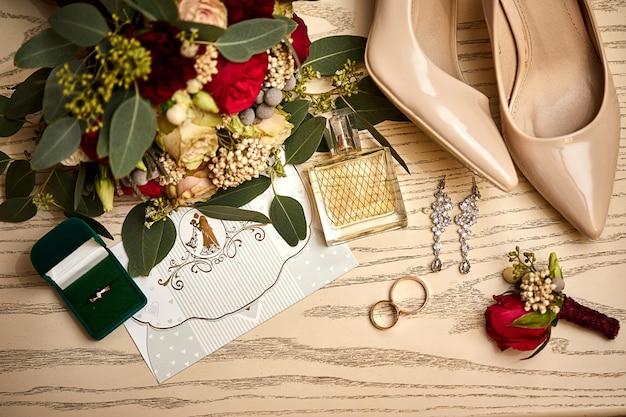 Des accessoires de mariée tels que des chaussures, un bouquet, une bague et un parfum se trouvent sur une table