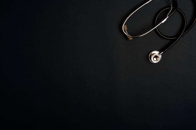 Accessoires de médecine stéthoscope, fond noir avec espace de copie.