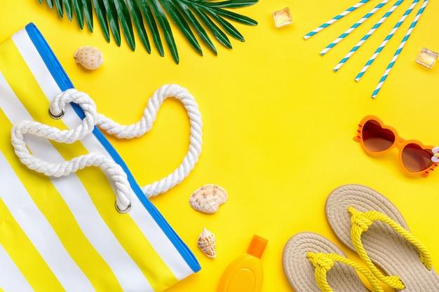Accessoires de natation - sac de plage tendance à rayures, crème solaire, lunettes en forme de cœur, tongs, paume, coquillages, tablette. vue de dessus à plat