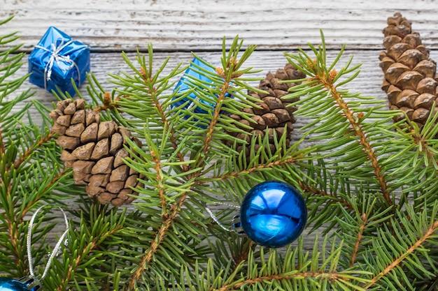 Accessoires de noël en bleu, cône et branches de sapin sur fond blanc en bois
