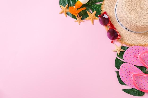 Accessoires de plage avec chapeau de paille, bouteille de crème solaire et étoile de mer sur fond rose vue de dessus avec espace de copie.