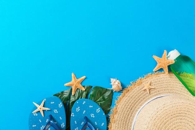 Accessoires de plage avec chapeau de paille et coquillages sur fond bleu vue de dessus avec espace de copie.