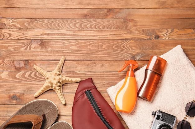 Accessoires de plage avec crème solaire sur fond de bois