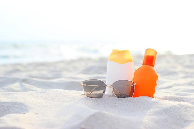 Accessoires de plage et crèmes solaires sur le sable du bord de mer. photo de haute qualité