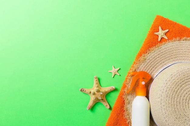Accessoires de plage d'été à plat. crème de bouteille de crème solaire, chapeau de paille, serviette et coquillages sur fond coloré. concept de vacances de voyage avec espace de copie.