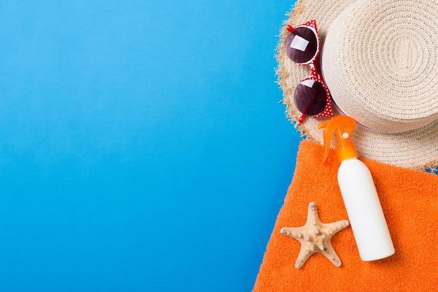 Accessoires de plage d'été à plat. crème de bouteille de crème solaire, serviette et coquillages sur fond coloré. concept de vacances de voyage avec espace de copie.