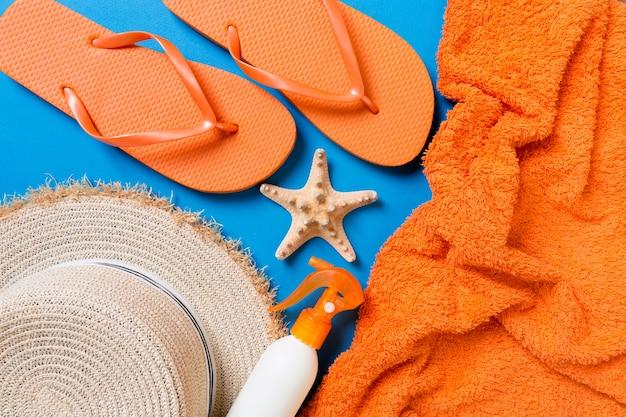 Accessoires de plage d'été à plat. crème solaire pour bouteille, chapeau de paille, tongs, serviette et coquillages sur fond coloré. concept de vacances de voyage avec espace de copie.