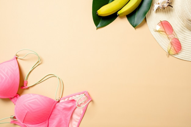 Accessoires de plage femme: chapeau de paille, lunettes de soleil, maillot de bain, banane sur fond jaune. concept de voyage, fond d'été.