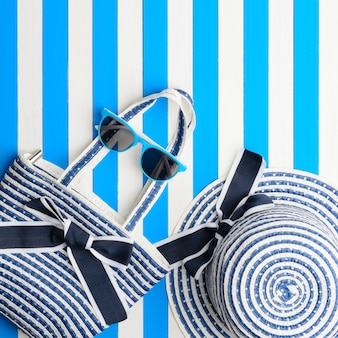 Accessoires de plage sur fond bleu et blanc. vue de dessus, mise à plat.