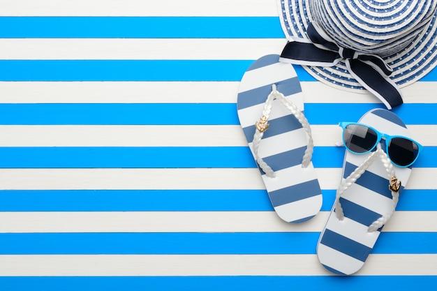 Accessoires de plage sur fond bleu et blanc. vue de dessus, pose à plat.