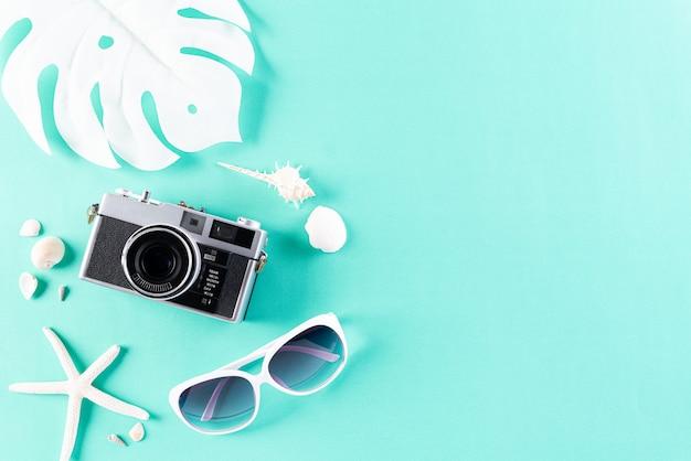 Accessoires de plage sur fond pastel vert pour le concept de vacances d'été.