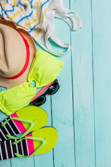 Accessoires de plage avec maillot de bain jaune, lunettes de soleil et tongs