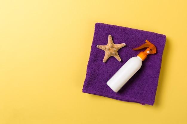 Accessoires de plage à plat avec espace de copie. serviette bleu violet et blanc, coquillages, chapeau de paille et une bouteille de crème solaire sur fond jaune. concept de vacances d'été
