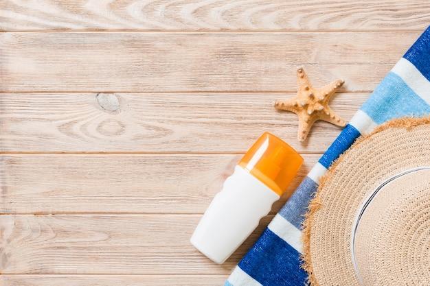 Accessoires de plage à plat avec espace de copie. serviette rayée bleu et blanc, coquillages, chapeau de paille et une bouteille de crème solaire sur fond de bois. concept de vacances d'été.