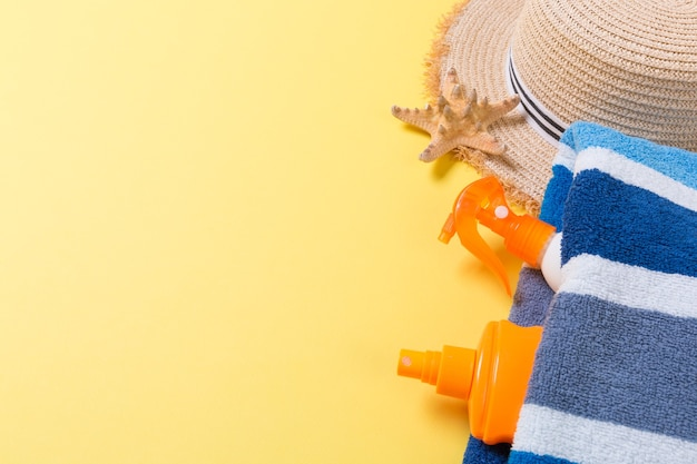 Accessoires de plage à plat avec espace de copie. serviette rayée bleu et blanc, coquillages, chapeau de paille et une bouteille de crème solaire sur fond jaune. concept de vacances d'été.