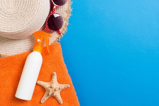 Accessoires de plage à plat d'été. bouteille de crème solaire, serviette et coquillages sur fond coloré. concept de vacances de voyage avec espace copie