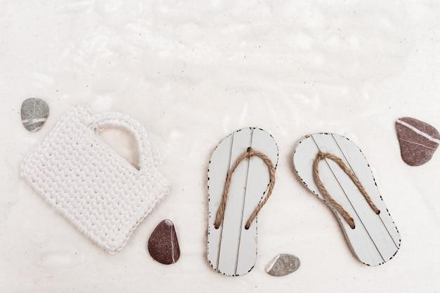Accessoires de plage pour femmes, sac tricoté blanc et sandales sur fond de sable blanc.