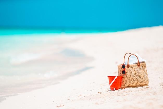 Accessoires de plage - sac de paille, chapeau et lunettes sur la plage