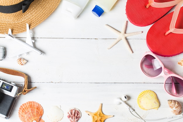 Accessoires de plage. sac, serviette, lunettes de soleil et bascules sur fond en bois. vue de dessus avec copie