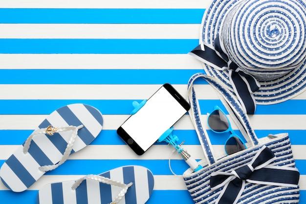 Accessoires de plage et smartphone sur blanc et bleu. vue de dessus, pose à plat.