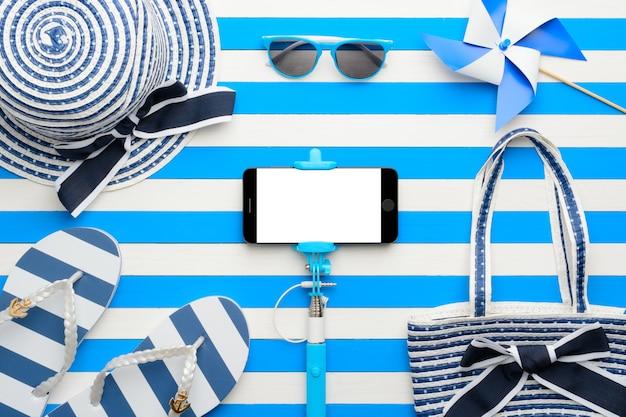 Accessoires de plage et smartphone sur fond blanc et bleu. vue de dessus, mise à plat.
