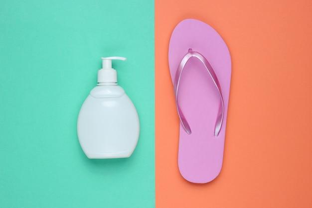 Accessoires de plage. tongs de plage rose à la mode, bouteille de crème solaire sur fond de papier bleu corail. mise à plat. vue de dessus