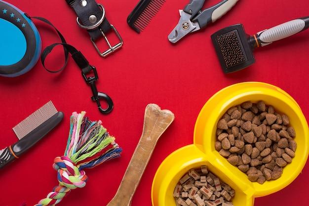 Accessoires pour animaux de compagnie sur fond rouge. vue de dessus. nature morte. espace de copie