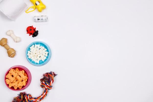 Accessoires pour animaux de compagnie, de la nourriture et des jouets sur fond blanc. plat poser. vue de dessus